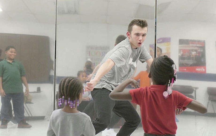 Hip hop dance teacher Ashton Gresham shows Milove Dorsey, 7, a few moves during a short break at the Boys & Girls Club in Peoria. Gresham, who lives in Delavan, has been teaching hip hop dance classes since January. Photo: Leslie Renken   Journal Star (AP)