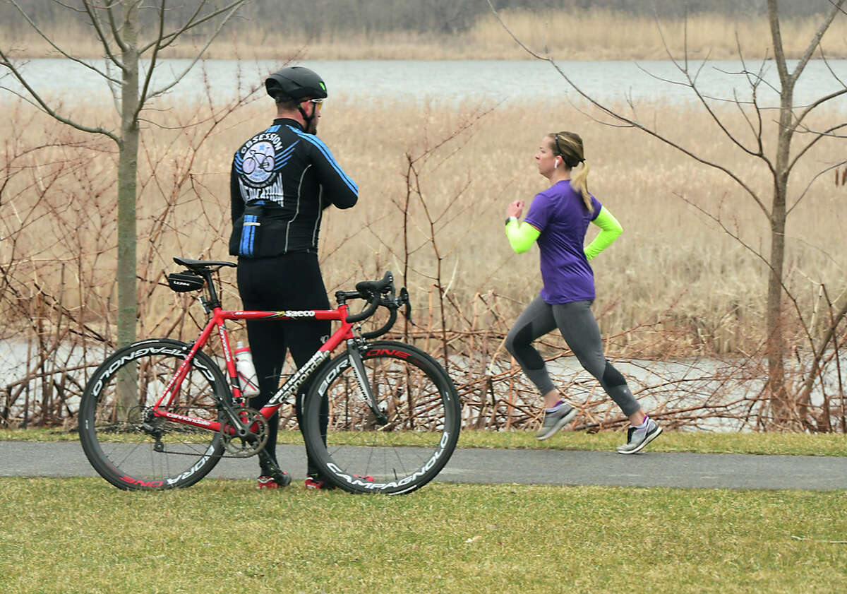 A bicyclist takes a break from riding as a jogger passes by him on the Mohawk-Hudson bike/hike trail on Friday, March 20, 2020 in Niskayuna, N.Y. (Lori Van Buren/Times Union)