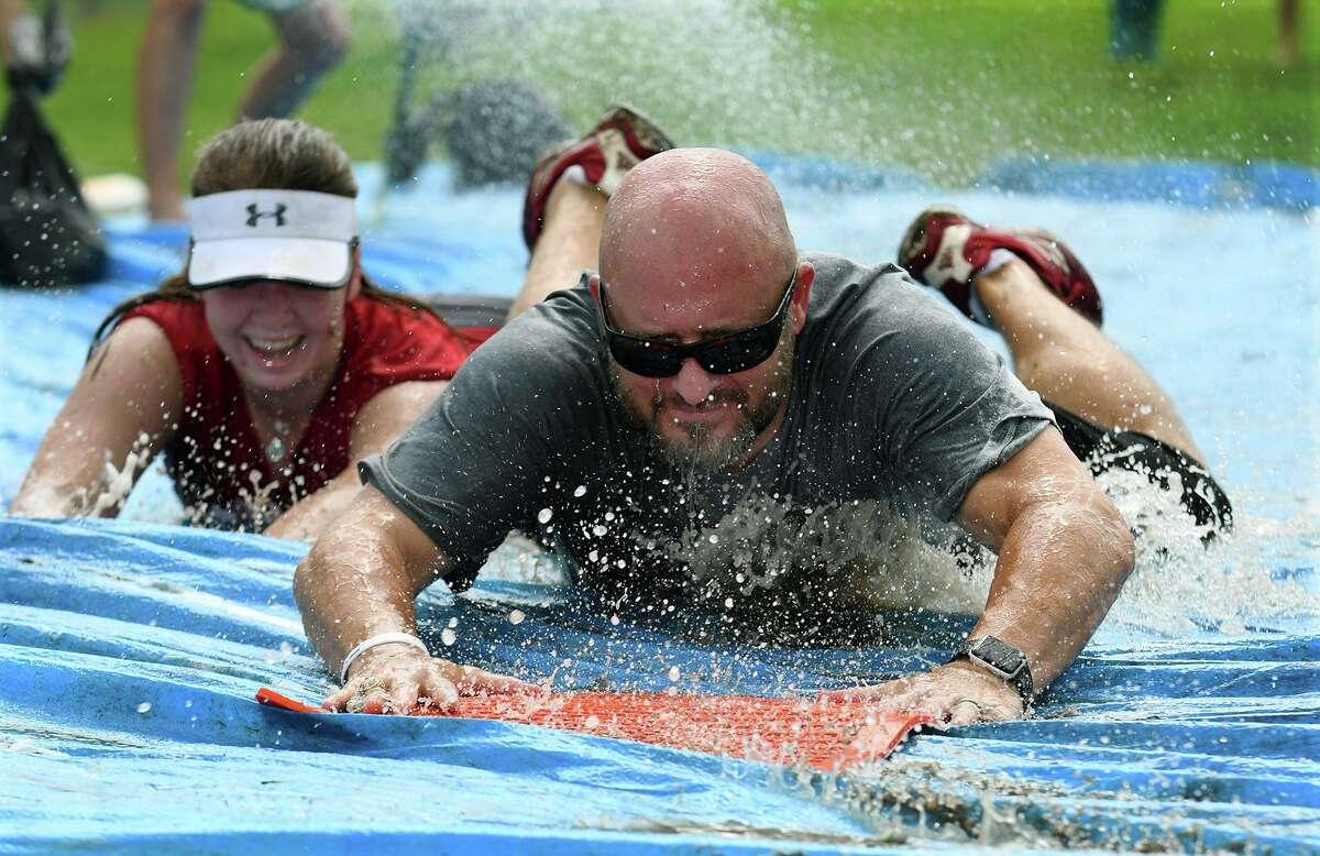 Tomball High School head softball coach Matt Marshall, right, and graduated senior Katie Ellington show off their sliding skills during the 2019 Tomball Cougar Softball Camp at THS on June 27, 2019.