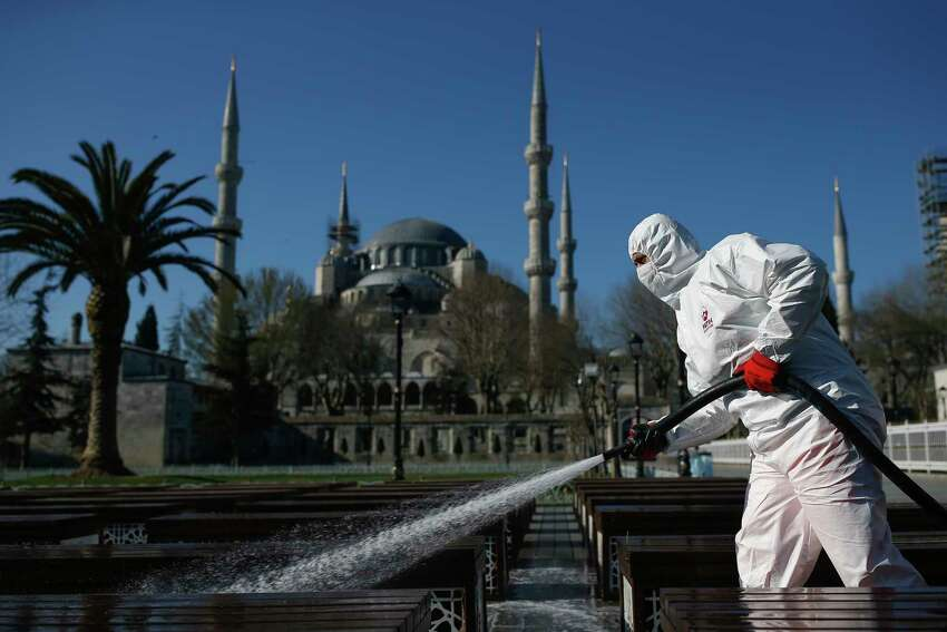 A municipality worker wearing a face mask and protective suits disinfects chairs outside the the historical Sultan Ahmed Mosque, also known as Blue Mosque, amid the coronavirus outbreak, in Istanbul, Saturday, March 21, 2020. The new COVID-19 coronavirus can cause mild or moderate symptoms, but for some it can cause severe illness.