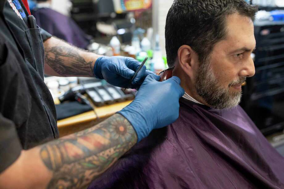 Rick's Barbershop, Rick Cummings, wears nylon gloves as he cuts Robert Fontenot's hair on Thursday, March 19, 2020. As of this morning, all barber shops are shut down. Photo: Gustavo Huerta, Houston Chronicle / Staff Photographer / Houston Chronicle © 2020