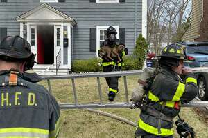 New Haven firefighters rescue a dog from a house fire on Ella T. Grasso Boulevard on March 21, 2020.