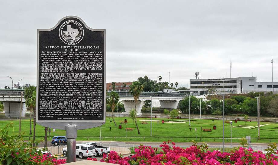 A view of a sign with the history of the Gateway to the Americas International Bridge, seen in the background, Friday, Mar. 20, 2020, after travel restrictions were announced at the U.S.-Mexico border amid concerns of COVID-19 Coronavirus spreading. Photo: Danny Zaragoza, Staff Photographer / Laredo Morning Times