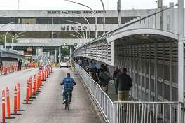 Pedestrians, motorists and cyclists cross the Gateway to the Americas International Bridge on Friday after travel restrictions at the U.S.-Mexico border were announced amid concerns of continued spreading of the coronavirus.