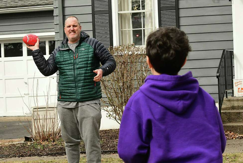 Larry Rulison, who is immune-compromised, throws a football in his front yard with his son Jack, 10, to get some exercise in on Friday, March 20, 2020 in Delmar, N.Y. His kids are homeschooling and Larry is working from home amid COVID-19 crisis. (Lori Van Buren/Times Union)