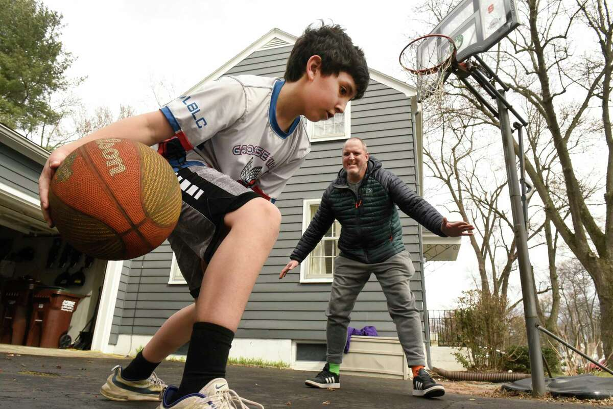 Larry Rulison, who is immune-compromised, plays basketball with his son Jack, 10, in their driveway to get some exercise in on Friday, March 20, 2020 in Delmar, N.Y. His kids are homeschooling and Larry is working from home amid COVID-19 crisis. (Lori Van Buren/Times Union)