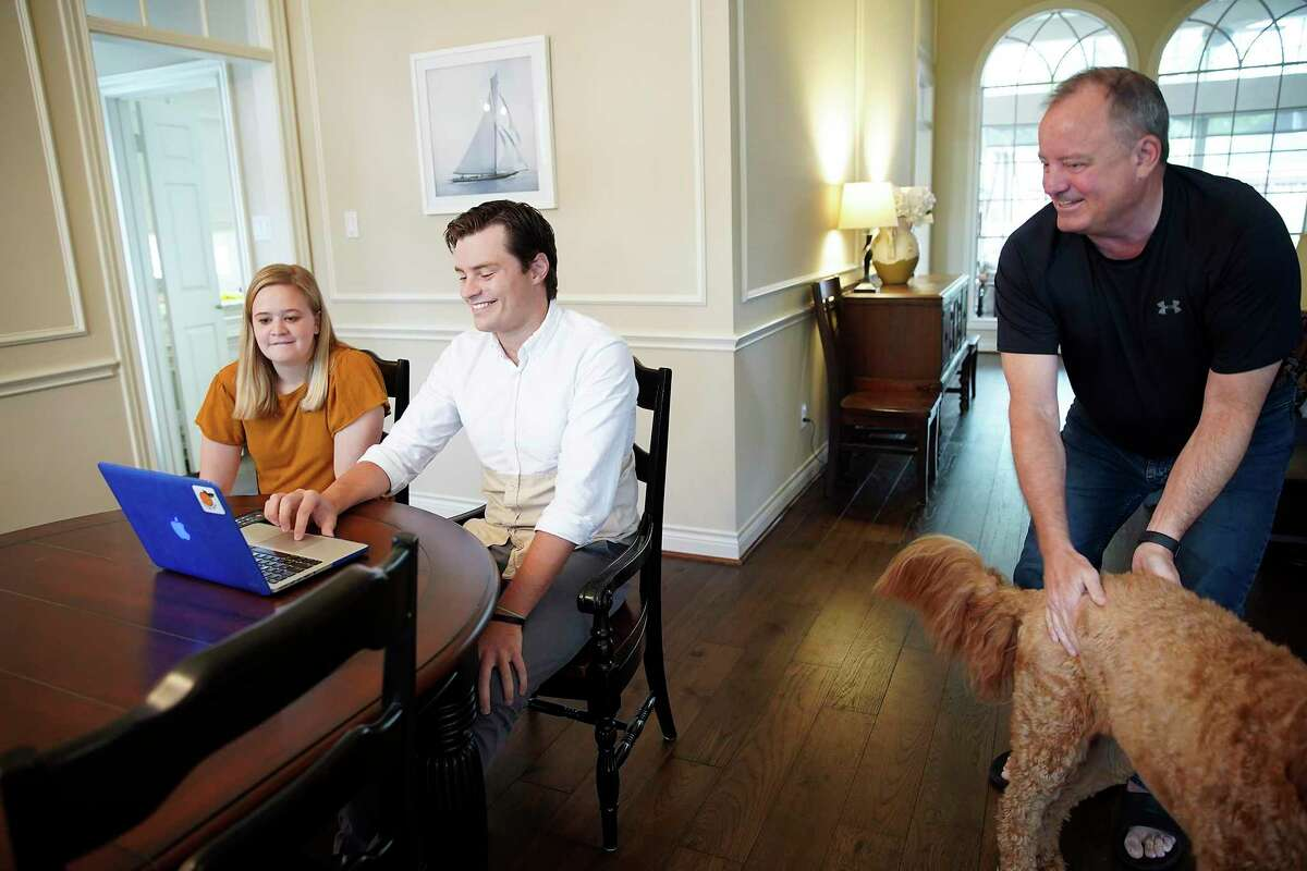 Baylor medical school student Andrew Jensen checks his laptop with his fiancé Annie Crea and dad, Leif, in his parent's Sugarland, Texas home on Friday, March 20, 2020.