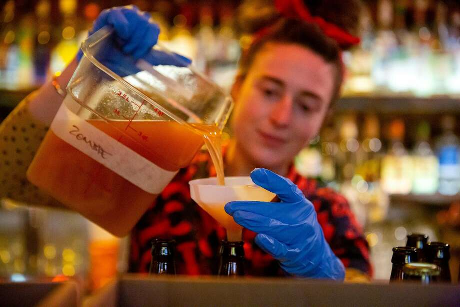 How we're drinking while sheltering in place: cocktail delivery. Here, Jeanie Grant, bar manager of Palmetto, pours a pre-mixed Zombie cocktail into bottles at the Kon-Tiki bar in Oakland, which began delivering drinks on Friday. Photo: Brittany Hosea-Small / Special To The Chronicle