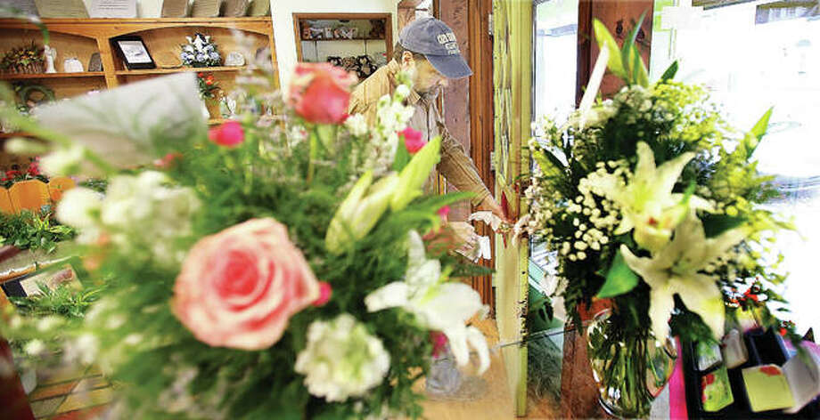 """Jeff Izard of Kinzels Flower Shop in Alton wipes down the front door as he and other businesses on Saturday prepared for Gov. J.B. Pritzker's """"Stay at Home"""" order through April 7. Florists aren't on the list of essential businesses allowed to remain open, meaning fresh flower deliveries had to be made by 5 p.m. Saturday."""
