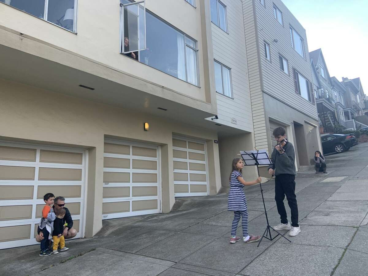 Staying well more than six feet away from others, a boy plays his violin for neighbors in San Francisco amid a shelter-in-place order to fight the spread of COVID-19 on Friday, March 20, 2020.