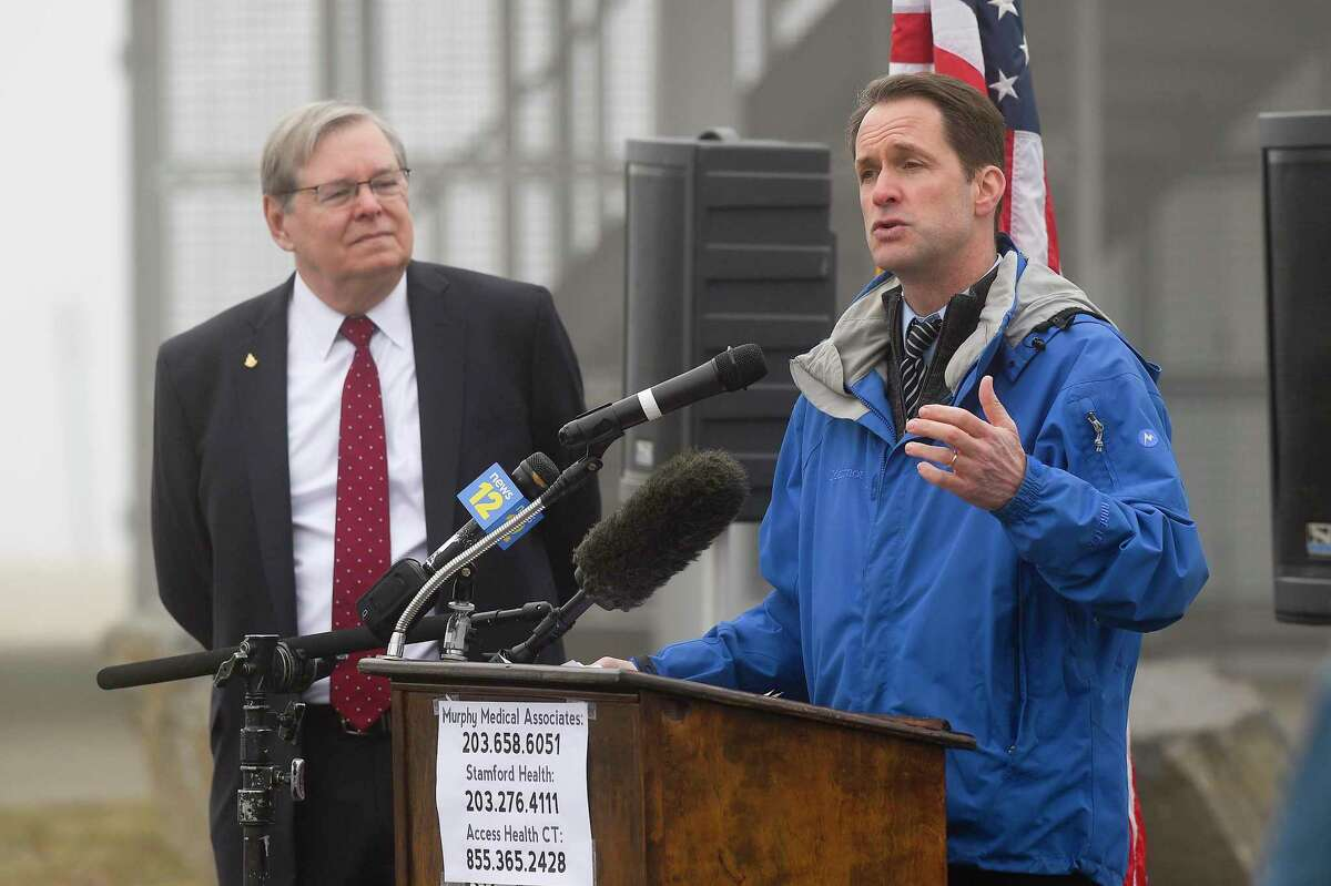 Stamford Mayor David Martin listens as Congressman Jim Himes speaks at a press conference as medical personnel from Murphy Medical Associates administer drive-thru screenings for the Covid-19 coronavirus at a mobile testing site set up at Cummings Beach in Stamford, Conn. , March 20, 2020.
