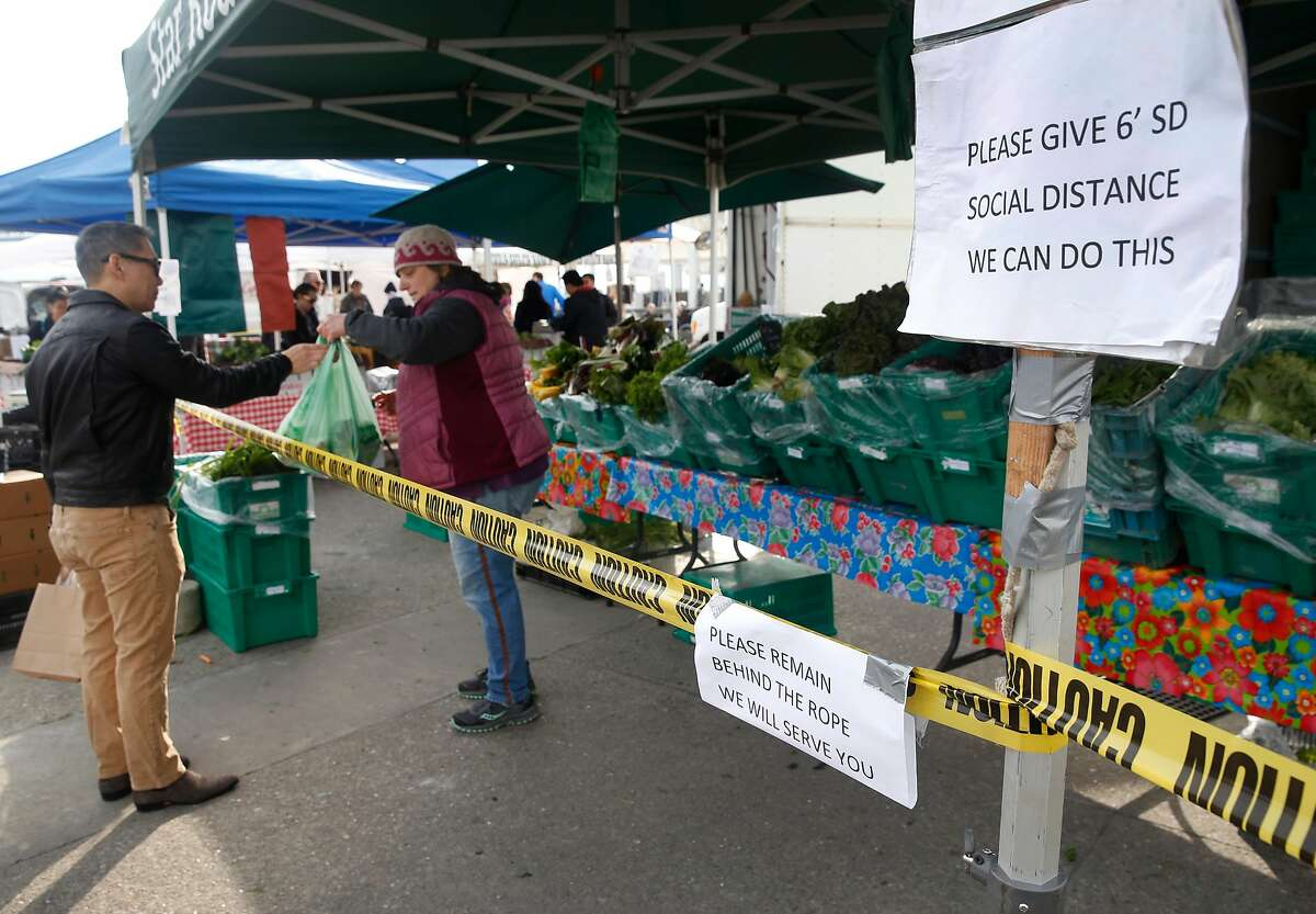 Patricia Buzzotta hands a bag of produce to a customer at the Star Route Farms stand in the Ferry Plaza Farmers Market in San Francisco, Calif. on Saturday, March 21, 2020 as the shelter in place order remains in effect to slow the spread of the coronavirus pandemic. Star Route Farms created a social distance zone in front of their stand.