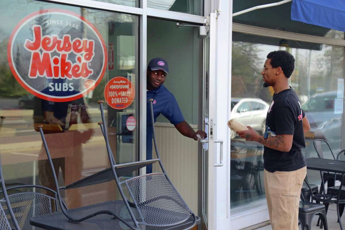 Ibrahim Olaosebikan of Jersey's Mike's in Westportgives a take-out order to Andrew Johnson on March 20, 2020.