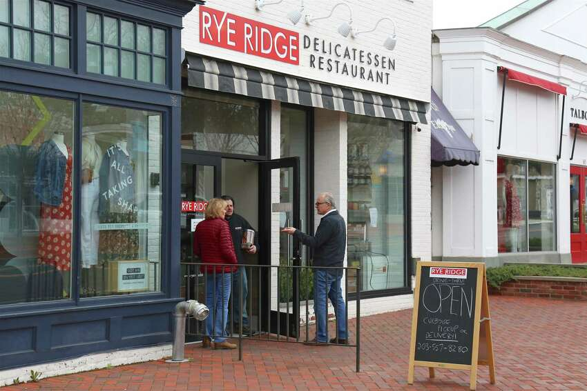 Rye Ridge Deli owner Scott Martin delivers a safe order to Peter and Janice Chingos of Westport on March 20, 2020, in down on Main Street in Westport.