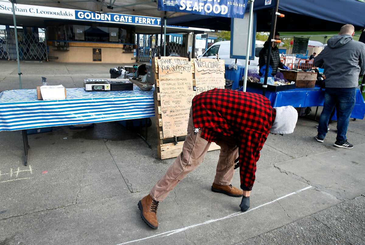 Oscar Patino draws a chalk line to mark a social distance safety zone in front of his seafood stand at the Ferry Plaza Farmers Market in San Francisco, Calif. on Saturday, March 21, 2020 as the shelter in place order remains in effect to slow the spread of the coronavirus pandemic.