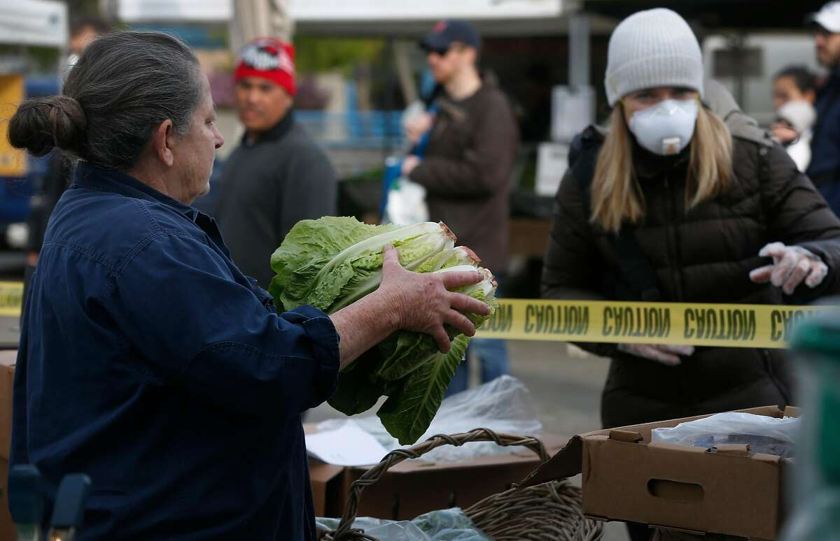 Annabelle Lenderink (left) hands lettuce to a customer at the Star Route Farms produce stand in the Ferry Plaza Farmers Market in San Francisco, Calif. on Saturday, March 21, 2020 as the shelter in place order remains in effect to slow the spread of the coronavirus pandemic. Star Route Farms created a social distance zone in front of their stand.