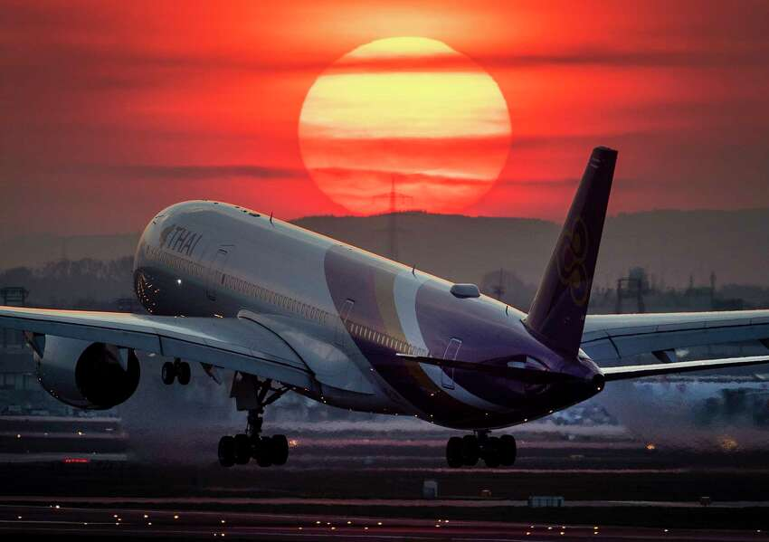 FILE - In this Tuesday, March 17, 2020 file photo, an airbus A 350 from Thai airways lands at the airport in Frankfurt, Germany, as the sun sets. Travel insurance can be a good investment if you have medical issues or you're traveling to a volatile region, experts say. But it has its limits, as many travelers whose plans are affected by coronavirus have found out. (AP Photo/Michael Probst, File)