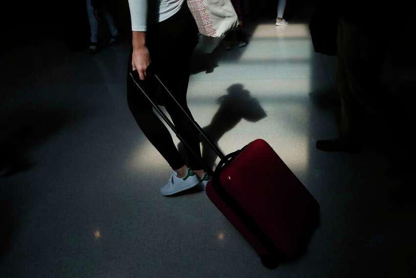 FILE - In this Nov. 27, 2019, file photo a traveler walks through the terminal at the Fort Lauderdale-Hollywood International Airport in Fort Lauderdale, Fla. Summer will be here soon, so it's a good time to start planning that vacation trip. Experts have plenty of tips for saving money on flights, lodging and other expenses. (AP Photo/Brynn Anderson, File)