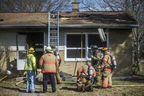 Firefighters with the Midland Fire Department secure the scene of a house fire at 3418 Sharon Street Saturday, March 21, 2020 in Midland. (Katy Kildee/kkildee@mdn.net)