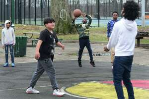 Youth play baskteball at Roodner Court housing complex on Thursday in Norwalk. Young people tend not to follow social distancing guidlines and still congregate frequently.