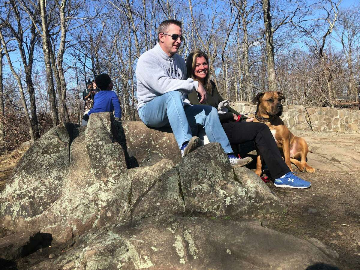 Lawrence McNellis and Jen Johnson sit with their dog, Dex, at the top of Mount Carmel in Sleeping Giant State Park Saturday March 21, 2020.
