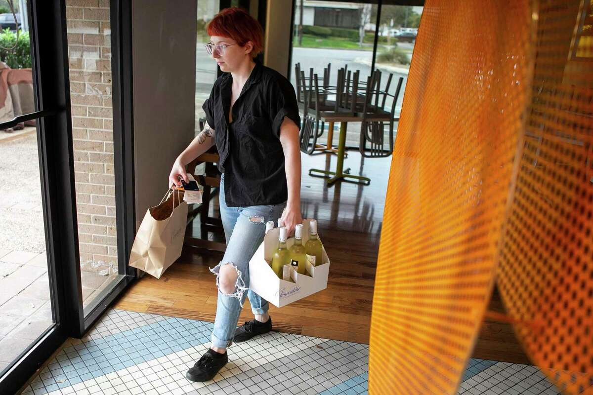 Sam Smagala takes a take out order to a customer at Clementine in San Antonio, Texas, on March 18, 2020. The restaurant has converted its service to take out only.