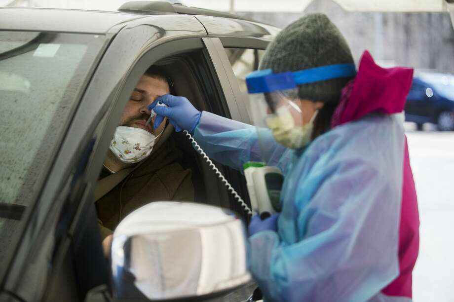 Kathleen Matson, an RN with MidMichigan Health, takes the temperature of Trevor Merryman of Sanford at an ambulatory testing center on the campus of MidMichigan Urgent Care – Midland on Saturday, March 21, 2020. In following CDC and Health Department guidelines, primary care providers first determine who is eligible for screening. Once deemed eligible, patients are given an appointment at the testing center, during which they remain in their car while a member of the MidMichigan Health care team meets them at the tent and tests for influenza and strep. If those tests are negative, a nasal swab is collected for COVID-19 testing. Those patients are then sent to their homes to remain in quarantine until their test results are reported to them. (Katy Kildee/kkildee@mdn.net) Photo: (Katy Kildee/kkildee@mdn.net)