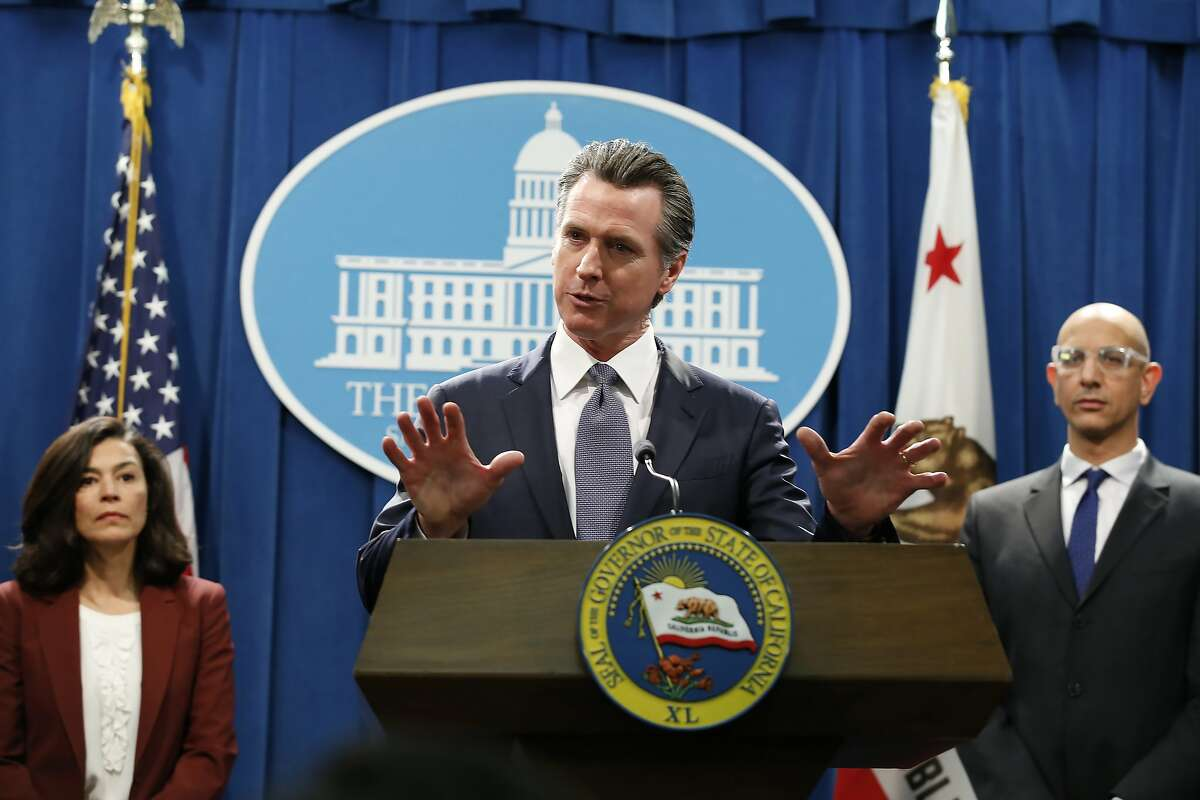 FILE - In this March 12, 2020 file photo, California Gov. Gavin Newsom speaks to reporters about the state's response to the coronavirus during a news conference in Sacramento, Calif. Newsom, a Democrat who leads the nation's most populous state, has won praise from both sides of the aisle for his approach to the coronavirus crisis though he's been less aggressive than some other governors and local leaders. Newsom is accompanied by California Department of Public Heath Director and State Health Officer Dr Sonia Angell, left, and California Health and Human Services Agency Director Dr. Mark Ghaly, right. (AP Photo/Rich Pedroncelli, File)