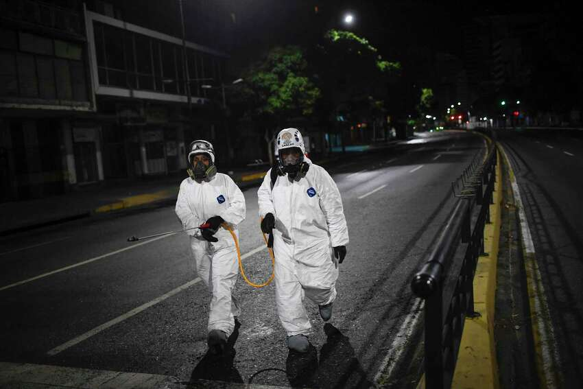 City workers walk after spraying disinfectant on the streets as a preventive measure against the spread of the new coronavirus, in Caracas, Venezuela, Saturday, March 21, 2020.