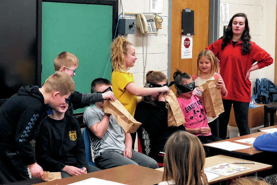 The Pike-Scott Agriculture in the Classroom program recently visited Griggsville-Perry Elementary School to teach its third-graders about pigs through a video and some hands-on activities with the help of Griggsville-Perry High School FFA student volunteer Kaylee Spencer. Spencer (right) supervised as students Henry Cooper (from left), Sam Scranton, Ben Bradshaw, Knox Dunham, Ruby Waters, Rayna Shaw, Daytlynn McCallister and Raina Williams played a game demonstrating how swine find food underground by using their sense of smell. Photo: Photo Provided
