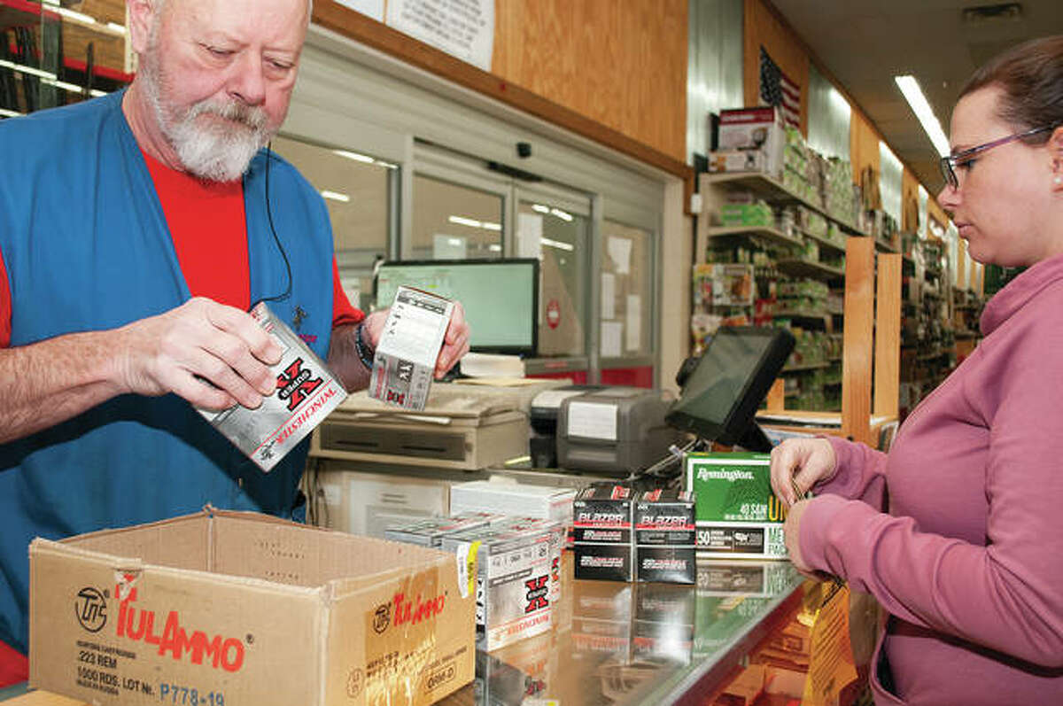 Gary Marlow (left) boxes up ammunition for Cassie Speaks on Friday afternoon while Speaks was shopping at Midland Farm & Home Supply. Speaks said that she was buying the ammunition because of the COVID-19 pandemic.
