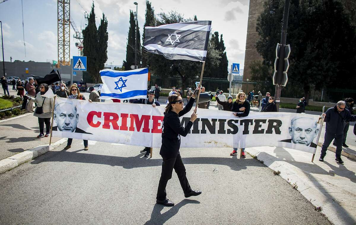 People wave Israeli flags during a protest outside the Israeli parliament in Jerusalem, Thursday, March 19, 2020. Hundreds of people defied restrictions on large gatherings to protest outside parliament Thursday, while scores of others were blocked by police from reaching the area as they accused Prime Minister Benjamin Netanyahu's government of exploiting the coronavirus crisis to solidify his power and undermine Israel's democratic foundations. (AP Photo/Eyal Warshavsky)