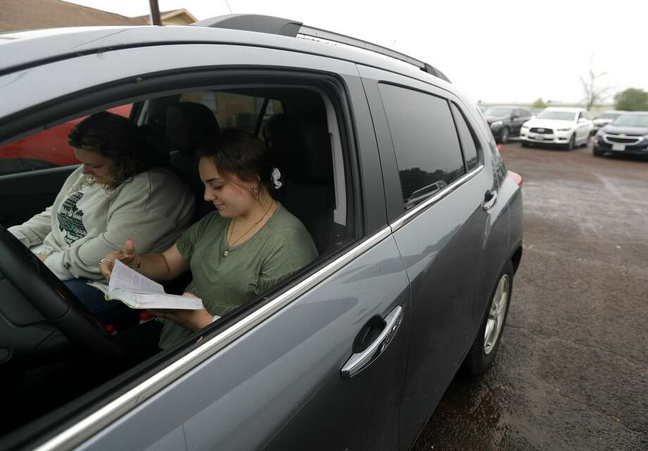 Megan McClelland reads her Bible along with the sermon of Pastor Chris Gober during a drive-in style service at First Montgomery Baptist Church, Sunday, March 22, 2020, in Montgomery. More than 200 parishioners attended the service. Photo: Jason Fochtman/Staff Photographer / Houston Chronicle  ? 2020