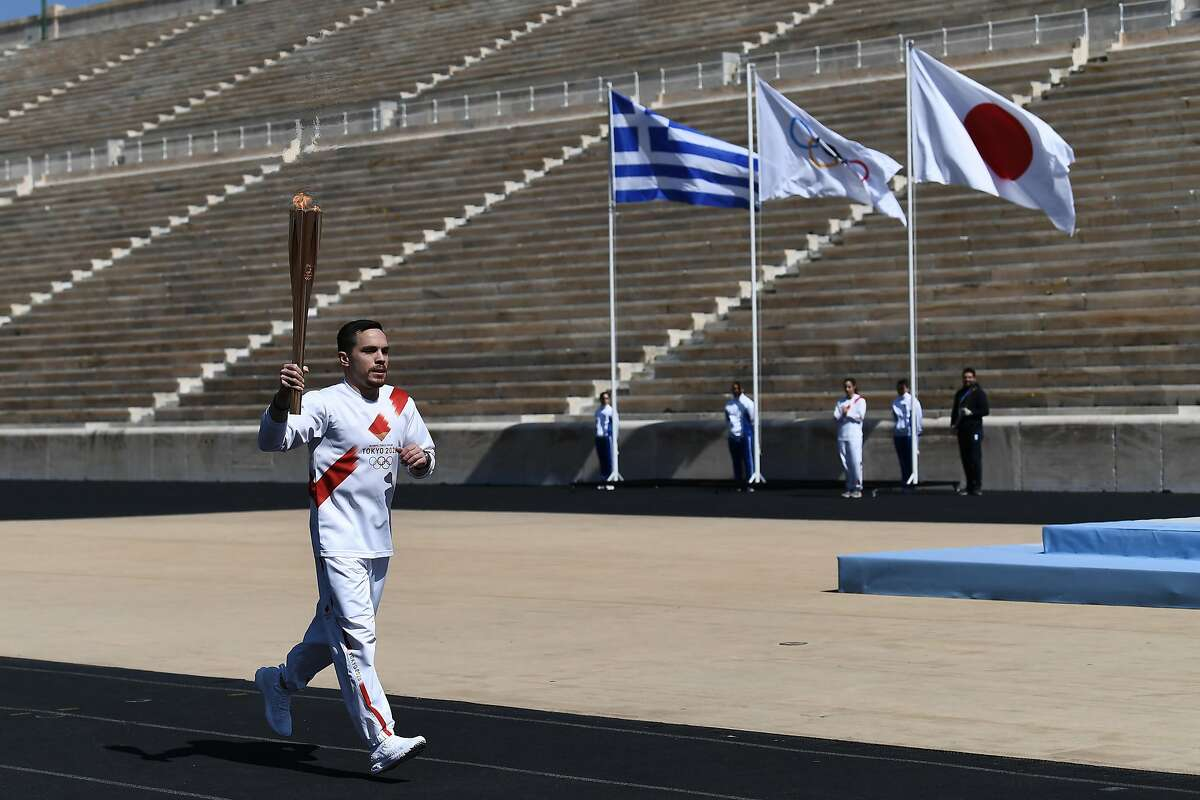 ATHENS, GREECE - MARCH 12: An Athlete carries the Olympic torch during the Flame Handover Ceremony for the Tokyo 2020 Summer Olympics on March 19, 2020 in Athens, Greece. The ceremony was held behind closed doors as a preventive measure against the Coronavirus outbreak. (Photo by Aris Messinis - Pool/Getty Images Europe)