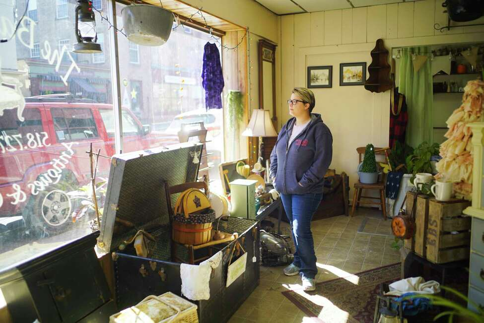 Jamie Peltier, co-owner of The Back Room, looks out her antique store front window on Sunday, March 22, 2020, in Cohoes, N.Y. Sunday was the last day for non-essential businesses to be open and Peltier is unsure how long they will be closed and if the store can financially survive during the closure. On Sunday everything at the store, which opened three years ago, was 50% off. (Paul Buckowski/Times Union)