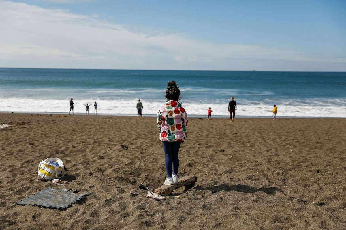 People try to maintain social distancing during the shelter-in-place orders at Rodeo beach on Sunday, March 22, 2020 in Marin County, California.