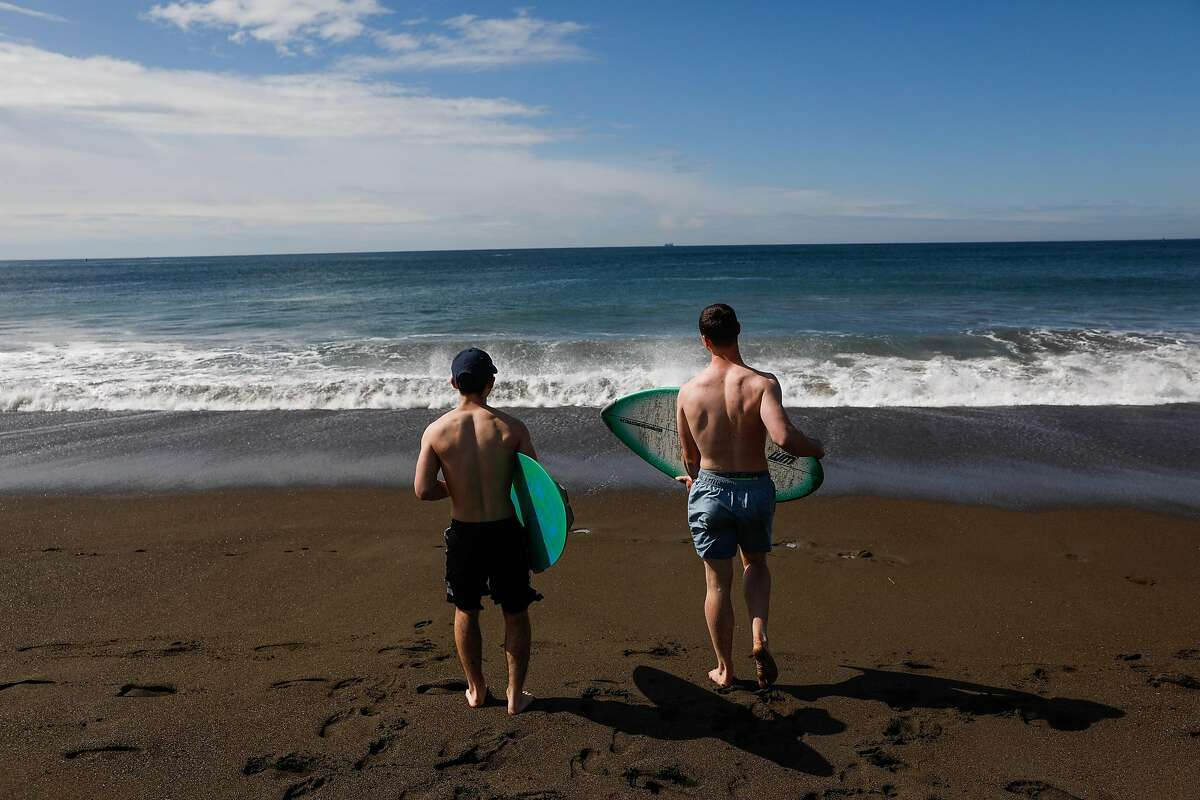 Travis Lateef and Red Ongaro (right) wakeboard during the shelter-in-place orders at Rodeo beach on Sunday, March 22, 2020 in Marin County, California.
