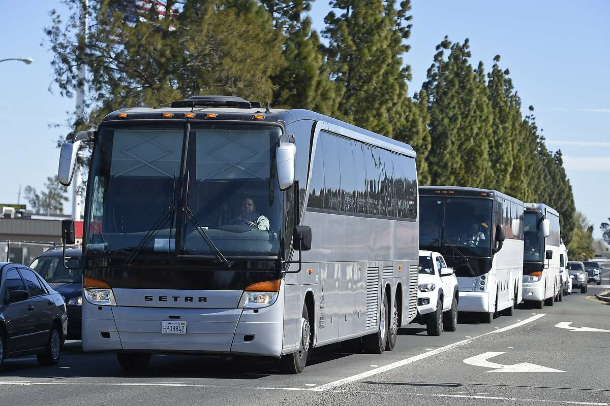 Three buses leave Travis Air Force Base carrying passengers that were aboard the Diamond Princess cruise ship in Japan after showing no symptoms of coronavirus in Fairfield, Calif., Monday, March 2, 2020. (Jose Carlos Fajardo/Bay Area News Group via AP)