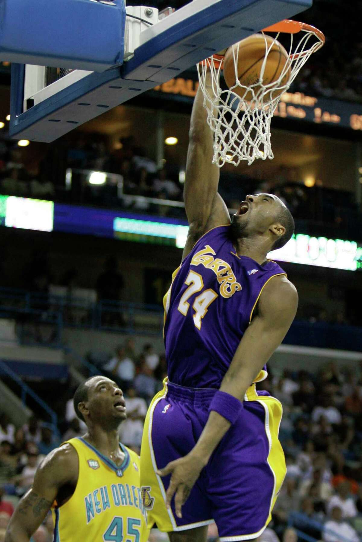 Los Angeles Lakers guard Kobe Bryant dunks as New Orleans Hornets forward Rasual Butler looks on in the first half of an NBA basketball game in New Orleans on Friday, March 23, 2007. (AP Photo/Alex Brandon)