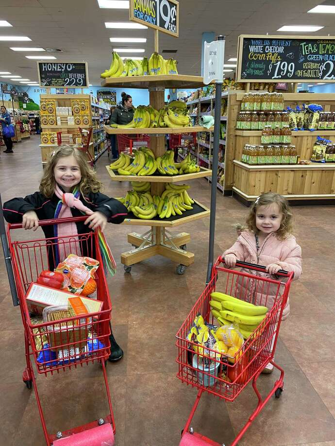 Chloe, left, and Lilly learn early at the supermarket. Photo: Lauren Robert-Demolaize / For Hearst Connecticut Media /