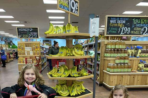 Chloe, left, and Lilly learn early at the supermarket.