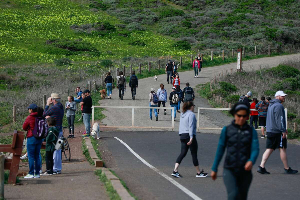 People try to maintain social distancing during the shelter-in-place orders at Rodeo beach on Sunday, March 22, 2020 in Marin County, California. Many surfers went out because they were concerned that beaches would soon be closed.