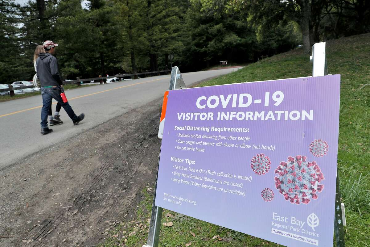 A sign informs visitors of coronavirus precautions as sparse crowds showed up at Tilden Regional Park as people get out of their homes during the statewide shelter in place in Berkeley, Calif., on Sunday, March 22, 2020.