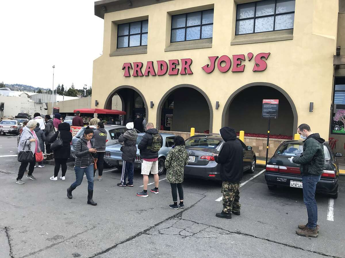 Customers line up during regular shopping hours at Trader Joe's on Lakeshore Ave. in Oakland, Calif. on Monday, March 15, 2020. Since the Coronavirus, many people in the Bay Area have tried to stock up on groceries and essentials fearing that businesses with run out.