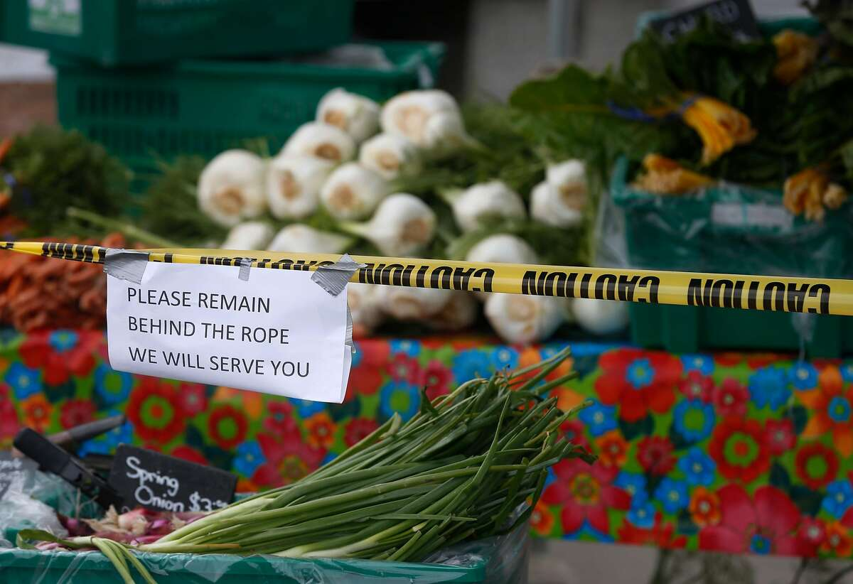 Star Route Farms created a social distance safety zone in front of their produce stand at the Ferry Plaza Farmers Market in San Francisco, Calif. on Saturday, March 21, 2020 as the shelter in place order remains in effect to slow the spread of the coronavirus pandemic.