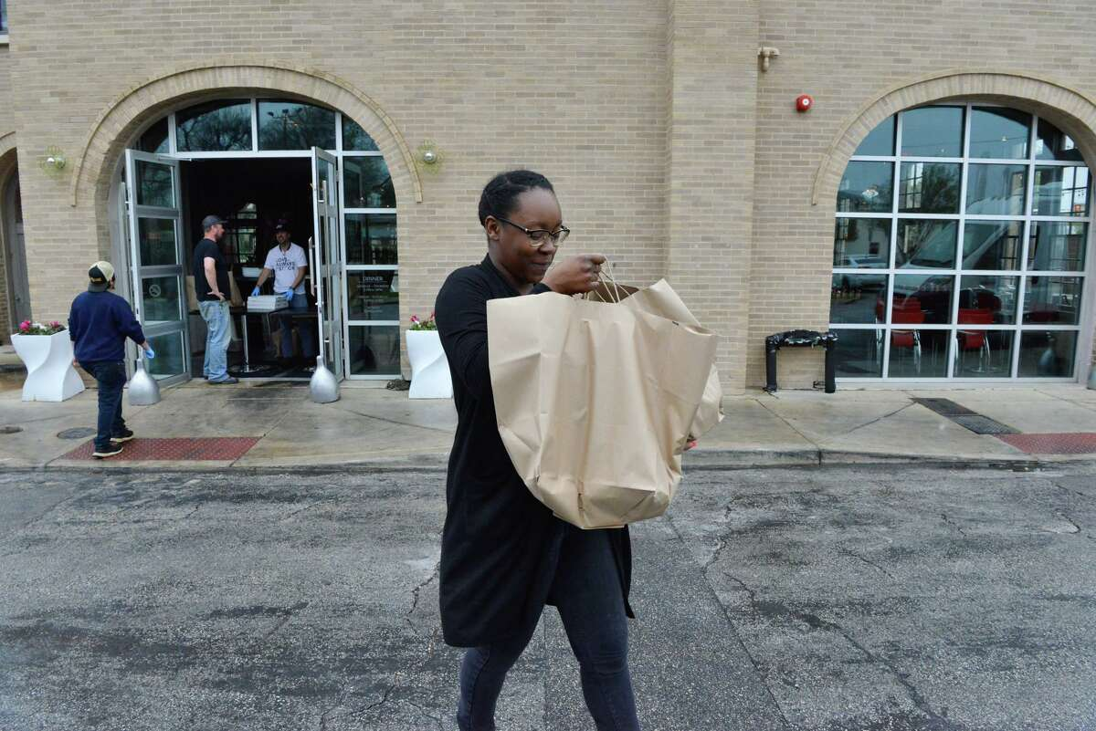 Ajisha Sutton who was laid off from the Holiday Inn Riverwalk looks over her bags of food during an outreach to service industry workers laid off during coronavirus stay-at-home orders.