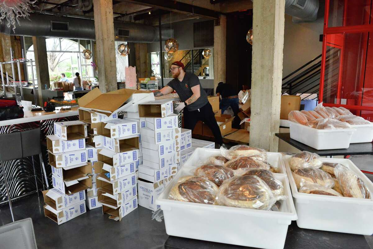 Josh Davis, the sous chef at Battalion, helps to sort and load bags of food donated Sunday, March 22, 2020, to restaurant workers who have been laid off or had their job hours cuts. Much of the food was donated by Food Related, a Schertz wholesaler to restaurants.