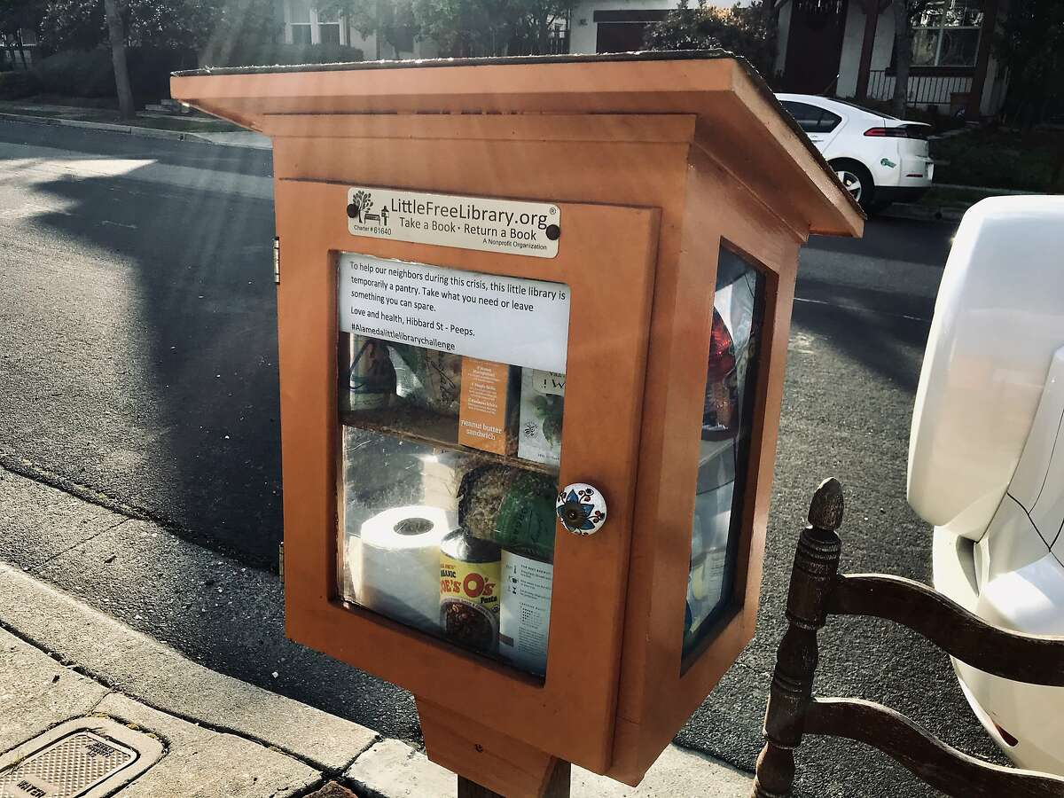 A Little Free Library in Alameda has been converted to a pantry, holding canned food, soap, toilet paper and Girl Scout cookies.