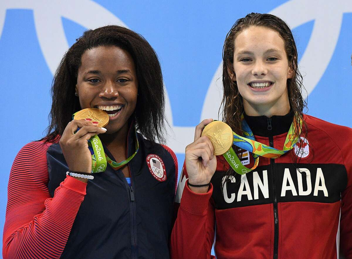 Canada's Penny Oleksiak, right, and United States' Simone Manuel celebrate their tie for gold in the women's 100-meter freestyle at the Summer Olympics in Rio de Janeiro, Brazil, early Friday, Aug. 12, 2016. (Sean Kilpatrick/The Canadian Press via AP)