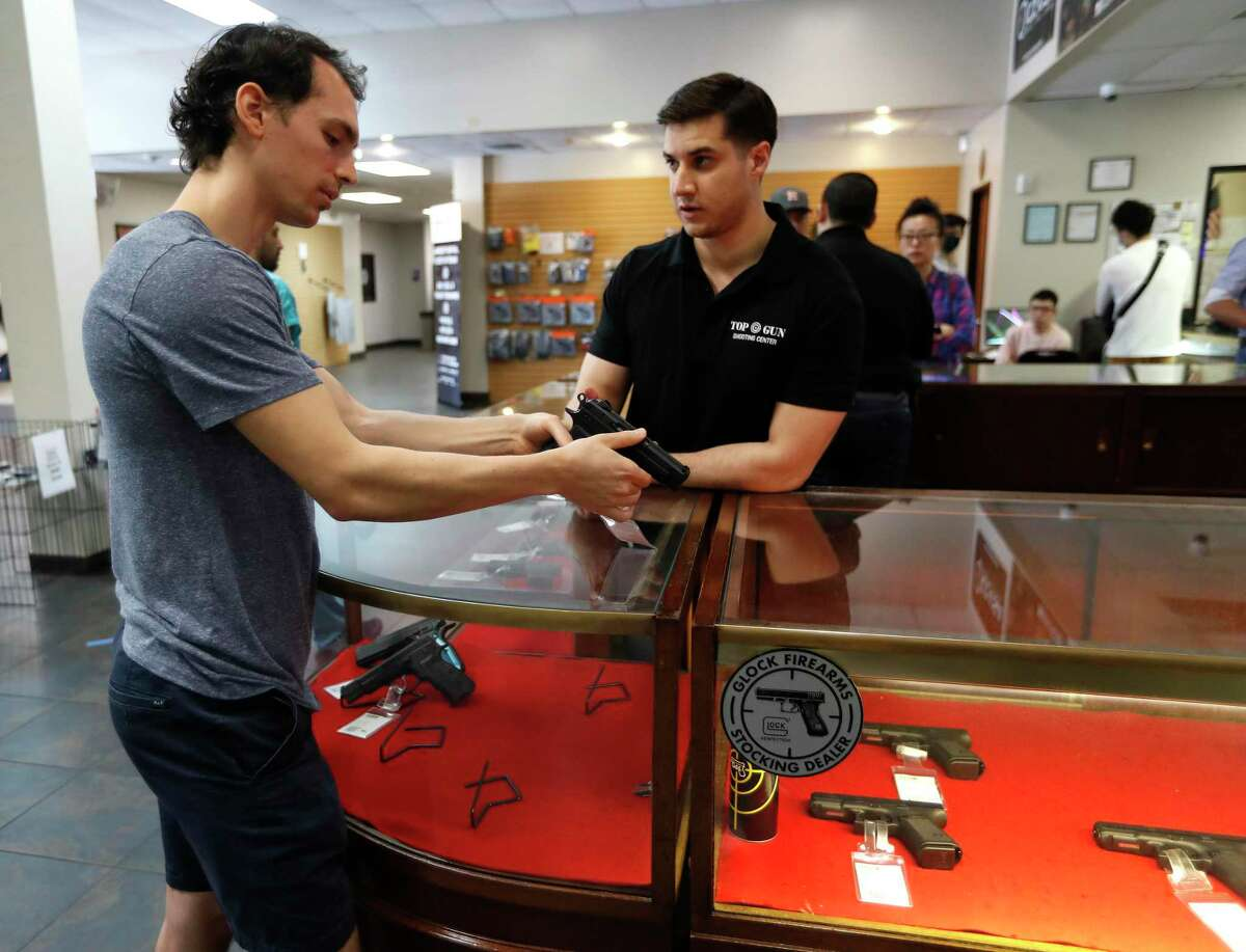 Aaron Andrus shops for a gun with the help of Louie Uribe, a sales associate at Top Gun Range, in Houston,Thursday, March 19, 2020. Gun sales have risen as people react to the uncertainty of the coronavirus pandemic.